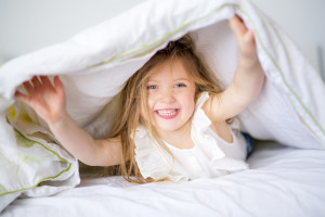 Adorable little girl waked up in her bed